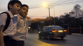 Two asian preteens waiting for the bus at outdoor stop in night city. He wants to get home. Shot on SONY A6300 in 4K UHD.