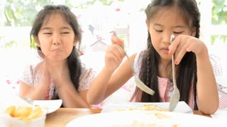 Two Asian pretty girls with fork in hands eats pasta, close-up