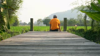 unidentified Asisn Man resting on wooden bridge, trip in nature