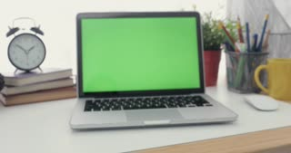 4K : A laptop computer with a key green screen set on work office table. Dolly in