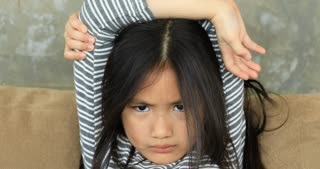 Angry girl when mother styling little girl's hair.