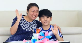 Asian child learning to folding Japanese paper origami with mother, art of paper folding.