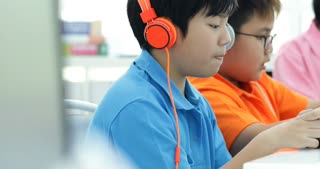 Asian child playing tablet computer together