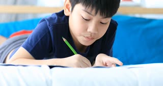 Asian Child writes homework at home .