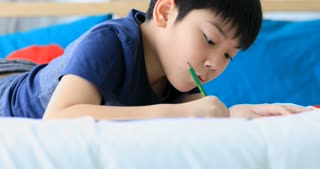 Asian Child writes homework at home .
