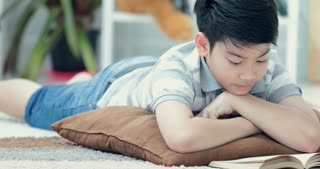 Asian cute boy reading a book on floor at home whit smile face