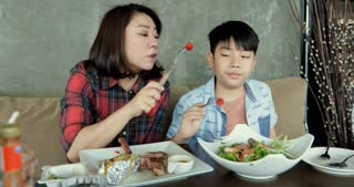 Asian family boy enjoy eating salad with your mom.