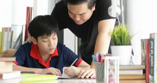Asian Father and son doing homework on the table in the living room .