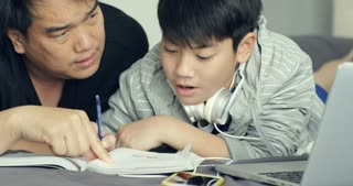 Asian father helps his young son while the boy is doing his homework at home
