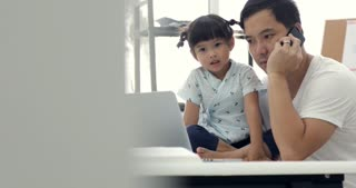 Asian modern family and little girl ,while dad works with notebook on work table at home office. caucasian.