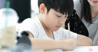 Asian Mom is helping her son to do homework of the school at home.