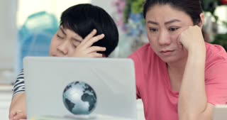 Asian mother and son be bored with learning and reading education from laptop computer.