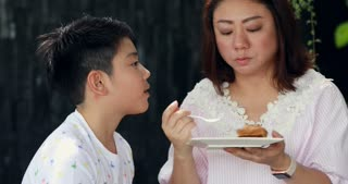 Asian Mother eats cake with his little son