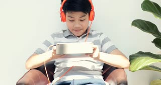Asian pre teens playing tablet computer with smile face at home.