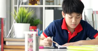 Asian preteens doing your homework with tablet computer with serious face.