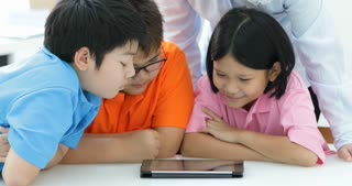 Asian teacher and Three kids entertaining themselves using digital tab and laughing