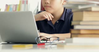 Asian teen boy using laptop computer at home, cute boy doing your homework with smile face.
