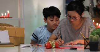 Asian Woman and child wrapping Christmas or other holiday handmade present in paper . She showing paper with smile face.