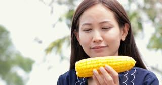Asian woman eats boiled corn