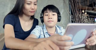 Asian woman with boy using tablet computer at cafe.