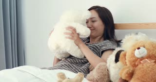 Asian woman with teddy bear on the bed.