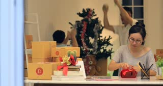 Asian Woman wrapping Christmas gift box or other holiday handmade present in paper . Happy family father and son dancing at background.