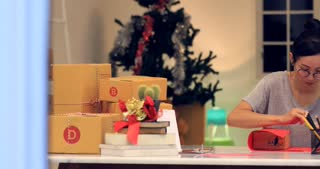 Asian Woman wrapping Christmas gift box or other holiday handmade present in paper . Making bow at gift box