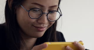 Attractive young asian woman working on cellphone at office with, closeup of hipster student girl browsing the internet, looking at monitor of modern computer, focus on the glasses