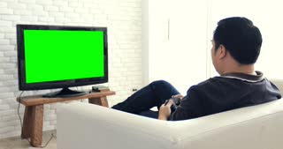 Back view of Asian man Play Computer Game Using with green screen on television.