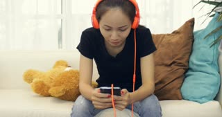 Beautiful asian woman listening to music earphones and using smartphone on couch at home relaxing lifestyle