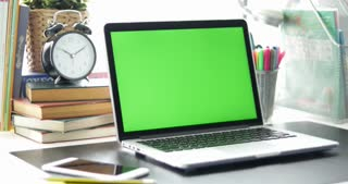 Black desk with a laptop, cell phone and digital tablet. Chroma key. Perfect to put your own images or videos. Dolly in.