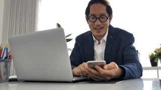 Business man in office  using laptop and cell phone, 4K Slow motion of office man talking and typing on mobile phone .