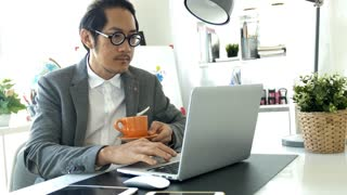 Businessman working on laptop computer in the office, 4K Slow motion asian business man wearing eyeglass in office.
