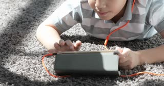 Close up of asian pre teens rest on floor and playing tablet computer with smile face at home.