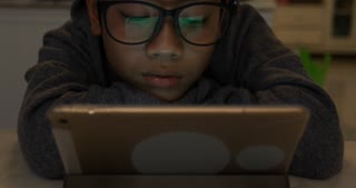 Close up of cute asian boy wearing eye glasses and using tablet computer ,Young teenage boy playing games on digital tablet .