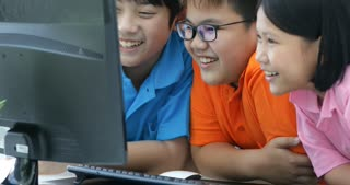 Close up of Smiling asian pupils using a desktop computer in the classroom with smile face.