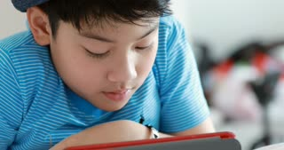 Closeup of face of 9 years old kid playing computer games lying in his bed in evening.