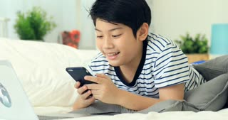 Cute asian boy hands holding smartphone and typewriter with smile face.