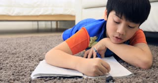 Cute asian boy rest on floor and doing homework at home with smile face.