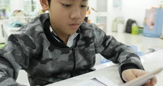 Cute asian boy using tablet computer ,Young teenage boy doing homework on digital tablet with smile face .