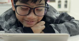 Cute asian boy wearing eye glasses and using tablet computer ,Young teenage boy playing games on digital tablet .