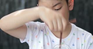 Cute asian child enjoy eating sweet dessert.