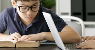 Cute asian teen boy doing your homework and looking a camera with smile face at home.