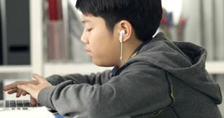 Cute asian teen boy doing your homework with laptop computer at home.