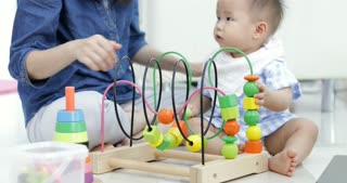 Cute little baby with mom. Mother and son playing education toy. boy and woman playing together.