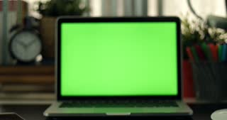 Dolly in of Laptop with green screen. Dark office.  Perfect to put your own image or video.Green screen of technology being used. Chroma Key laptop