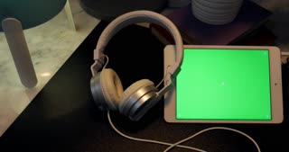Dolly shoot of Green Screen on Digital tablet and headphones on desk at night,