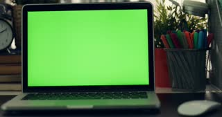 Dolly shoot of laptop with green screen. Dark office.  Perfect to put your own image or video.Green screen of technology being used. Chroma Key laptop