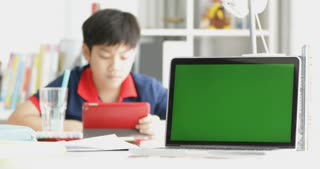 Green screen on laptop computer and asian boy watching on tablet computer on background