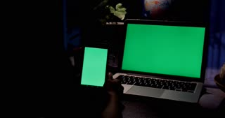 Hand using Smartphone and a Laptop Computer With Green screen . Dolly in